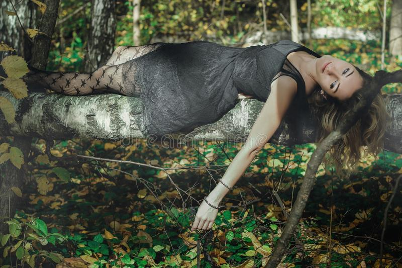 A young kind witch in a black dress with a black mask in a mystical forest in various poses. Art processing.  royalty free stock photo