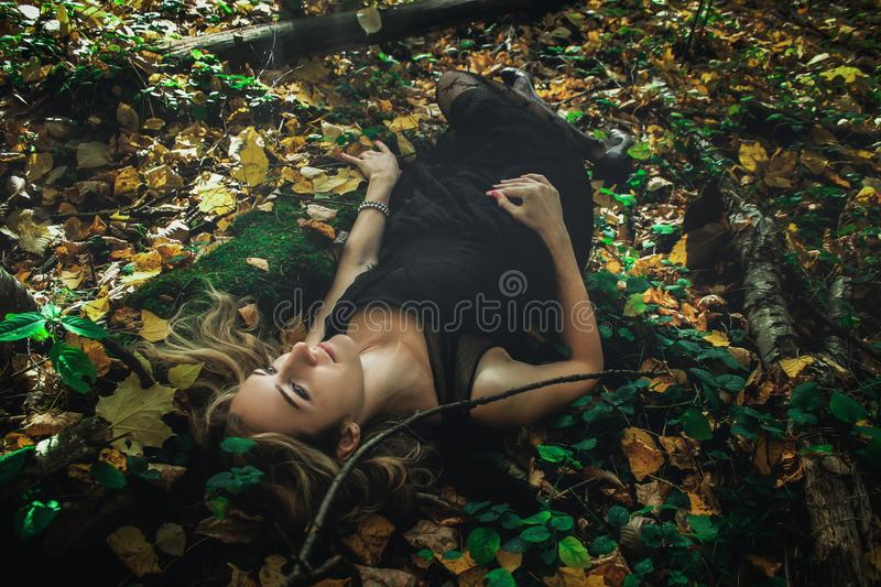 A young kind witch in a black dress with a black mask in a mystical forest in various poses. Art processing.  royalty free stock photography