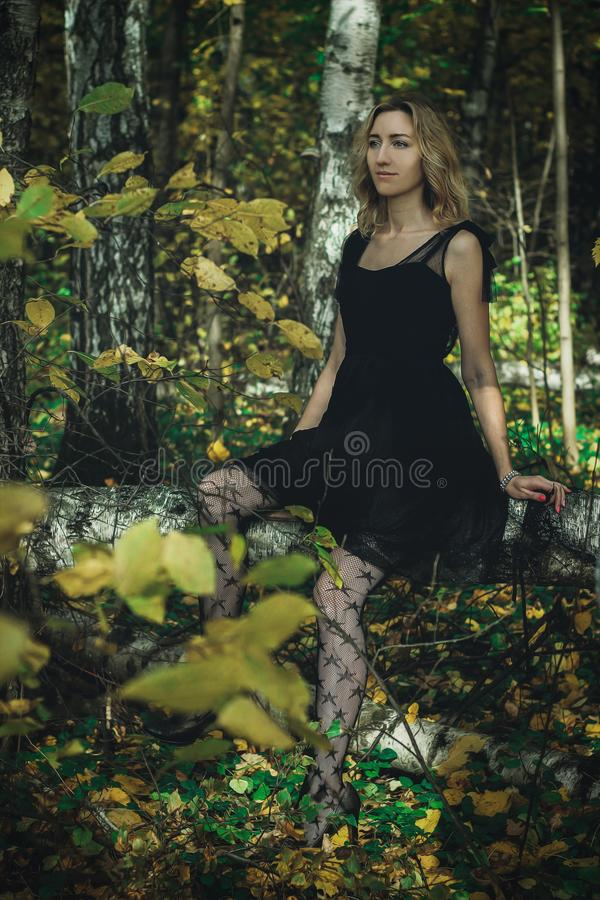 A young kind witch in a black dress with a black mask in a mystical forest in various poses. Art processing.  stock photo