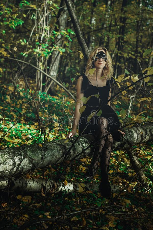 A young kind witch in a black dress with a black mask in a mystical forest in various poses. Art processing.  stock photos
