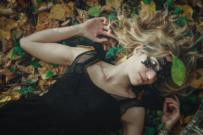 A young kind witch in a black dress with a black mask in a mystical forest in various poses. Art processing.  royalty free stock image