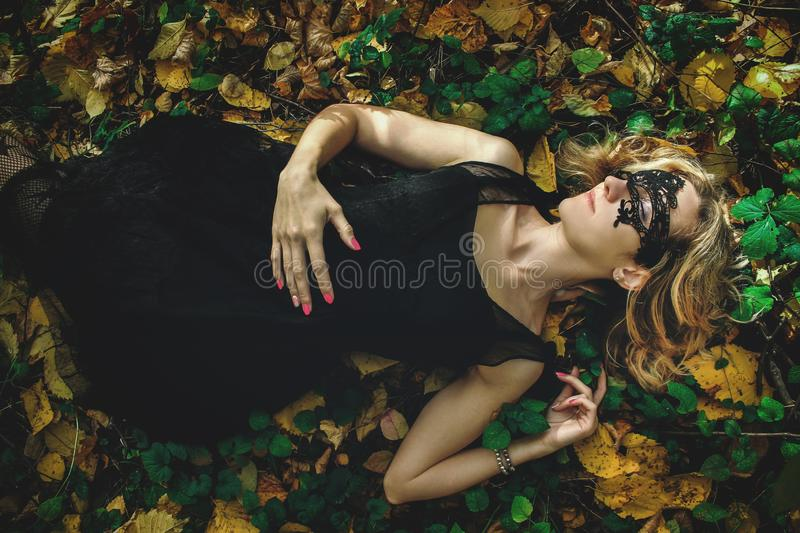 A young kind witch in a black dress with a black mask in a mystical forest in various poses. Art processing.  stock photography