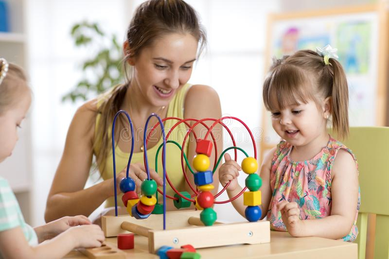 Young kindergarten teacher helping kids with toys royalty free stock photos