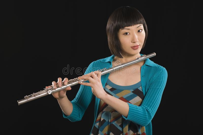 Young Korean Woman Holding Flute. Portrait of a woman playing flute isolated over black background royalty free stock photos