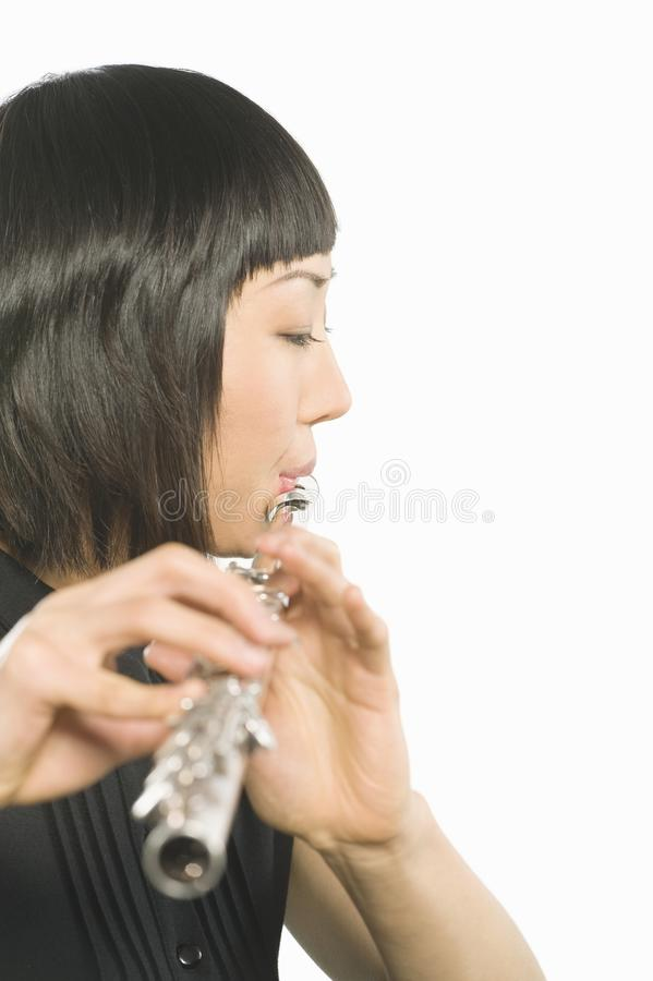 Young Korean Woman Playing Flute. Side view of female artist playing flute isolated over white background royalty free stock photo