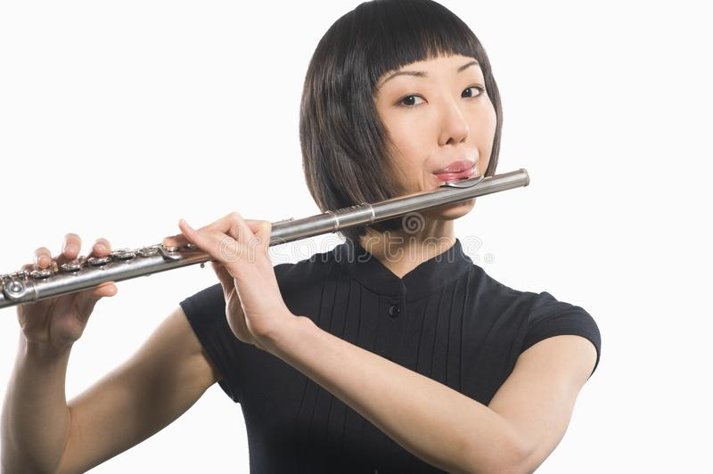 Young Korean Woman Playing Flute. Portrait of a female Flutist playing flute isolated over white background royalty free stock photos