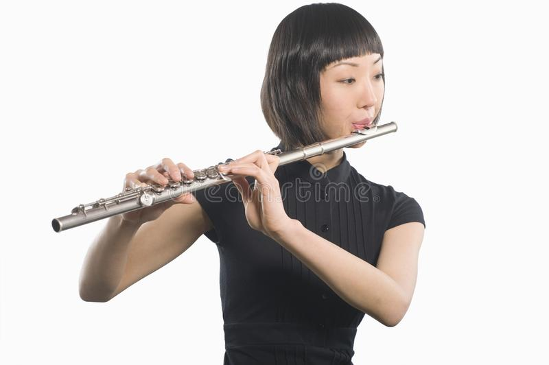 Young Korean Woman Playing Flute. Beautiful woman playing flute isolated over white background royalty free stock images