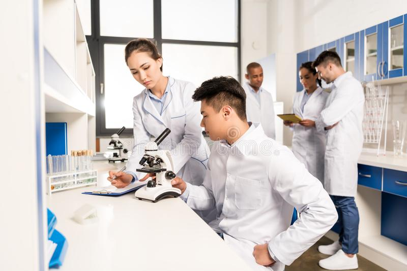 Young lab technicians working with microscope and taking notes about analysis stock photos