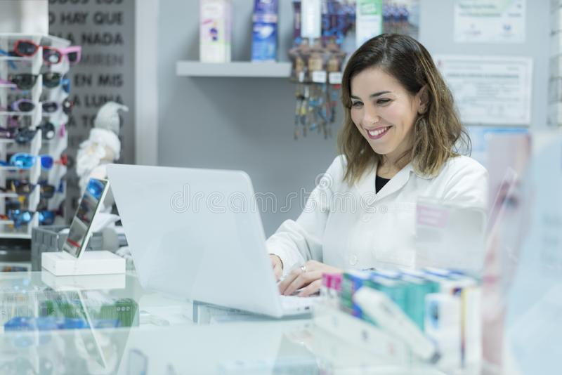 Young lab worker at laptop in optometry royalty free stock images