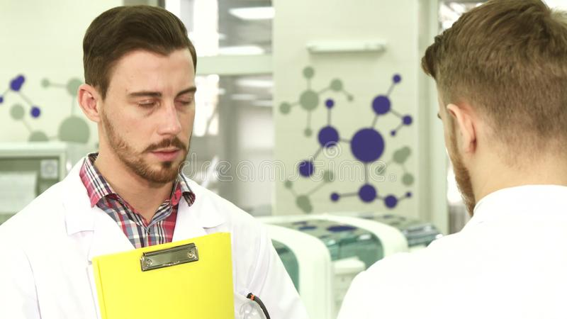 Young laboratory workers conduct serious negotiations about work stock photography
