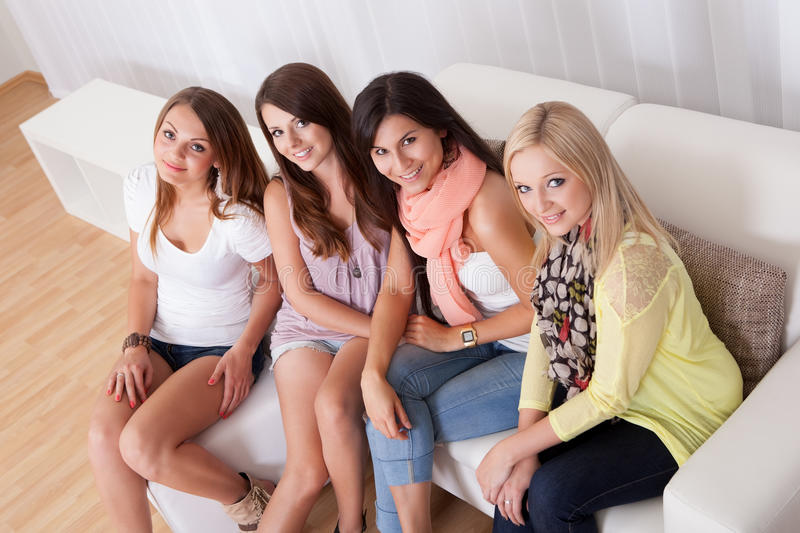 Young ladies sitting on a couch at home. Row of beautiful stylish young ladies sitting on a couch in a living room royalty free stock image