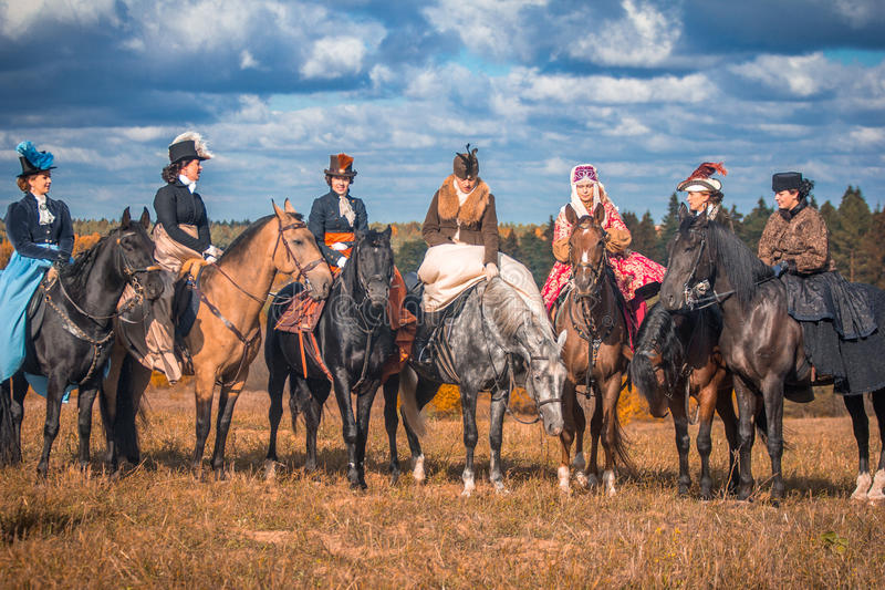 Young ladies in 19th century dresses riding horseback. Young pretty ladies standing close to each other. Nineteenth century dress. Autumn hunting with horses and royalty free stock photos