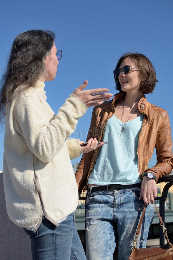Young ladies tourists have a stop at a bridge in Saint Petersburg, Russia and discuss further sightseeing royalty free stock image