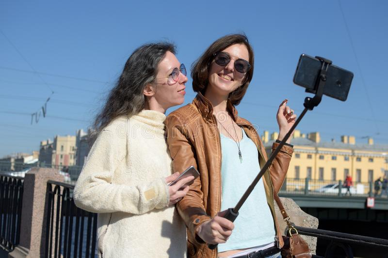 Young ladies tourists make selfies at a bridge in Saint Petersburg, Russia, and have fun in front of camera stock photo