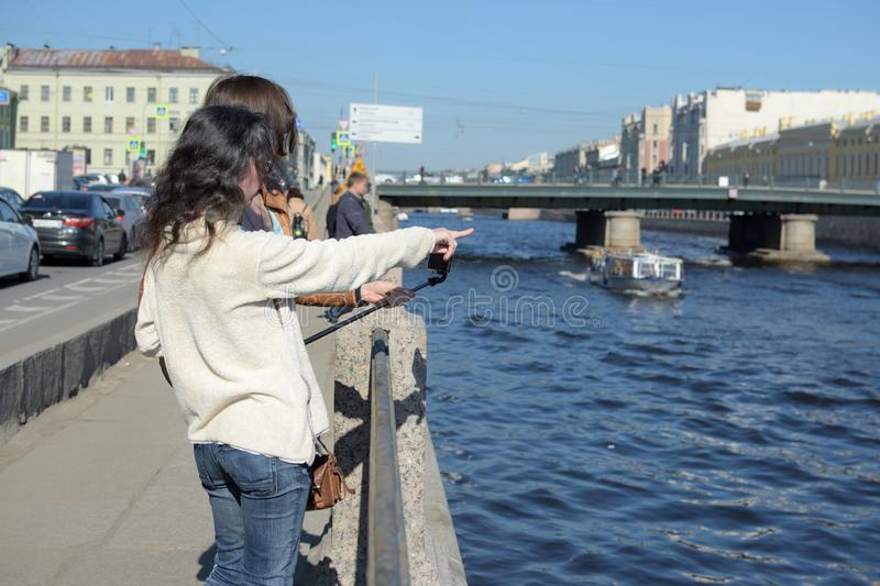 Young ladies tourists in Saint Peteresburg Russia enjoy summer on a sunny day and greet sightseeing boats stock images