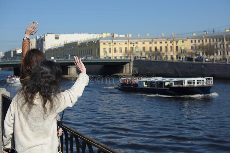 Young ladies tourists in Saint Peteresburg Russia enjoy summer on a sunny day and greet sightseeing boats stock photos