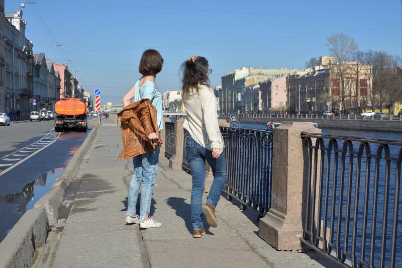 Young ladies tourists in Saint Petersburg Russia have fun together on a sunny day, undress and jump of joy royalty free stock images