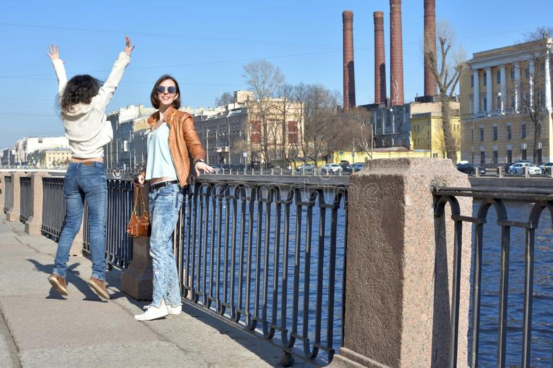Young ladies tourists in Saint Petersburg Russia have fun together on a sunny day, undress and jump of joy royalty free stock image