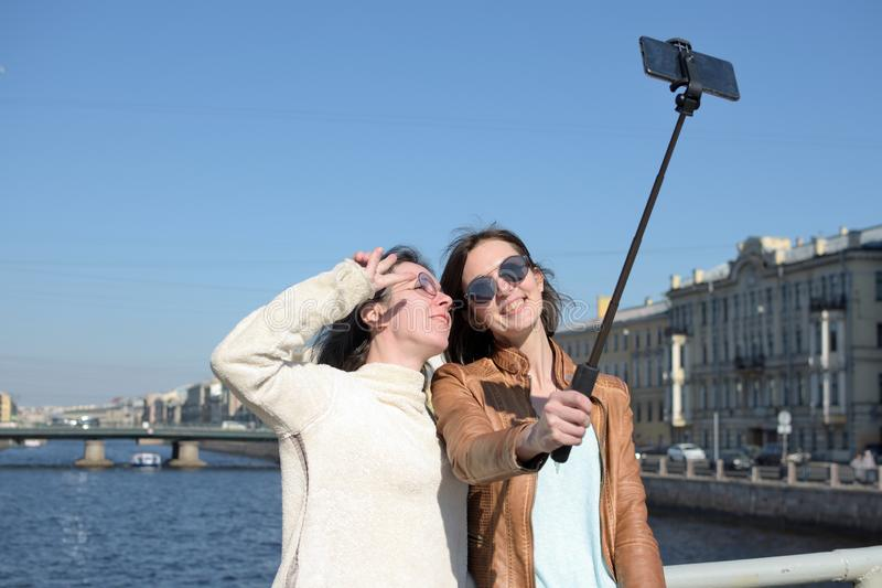 Young ladies tourists in Saint Petersburg Russia take selfies on a wooden bridge in the historical city center royalty free stock photo
