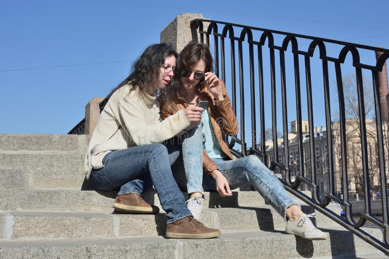 Young ladies tourists sitting together on stair at Fontanka river embankment in Saint Petersburg Russia watching tourist boats on stock photo