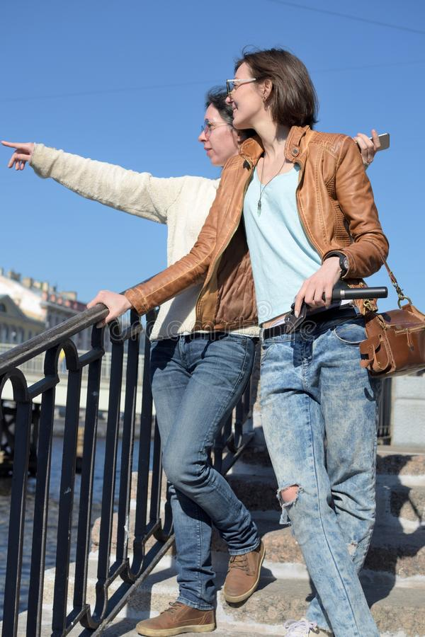 Young ladies tourists stand on Fontanka river embankment in Saint Petersburg Russia and point to a landmark royalty free stock image