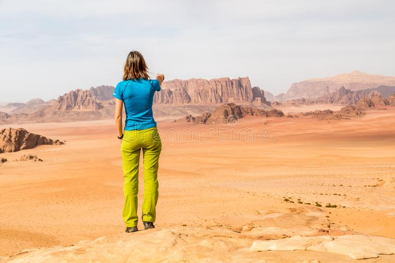 Young lady above desert pointing to red sand dunes, Wadi Rum, Jordan stock photos