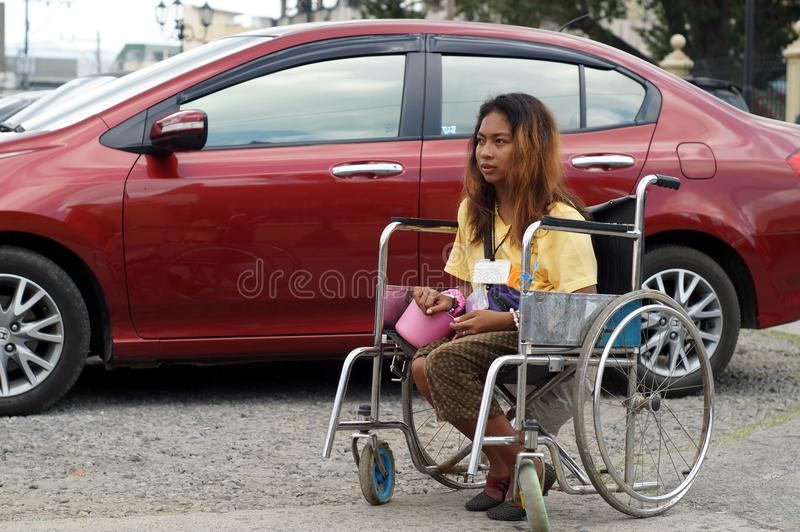 Young lady beggar on wheelchair begs at church parking lot stock photography