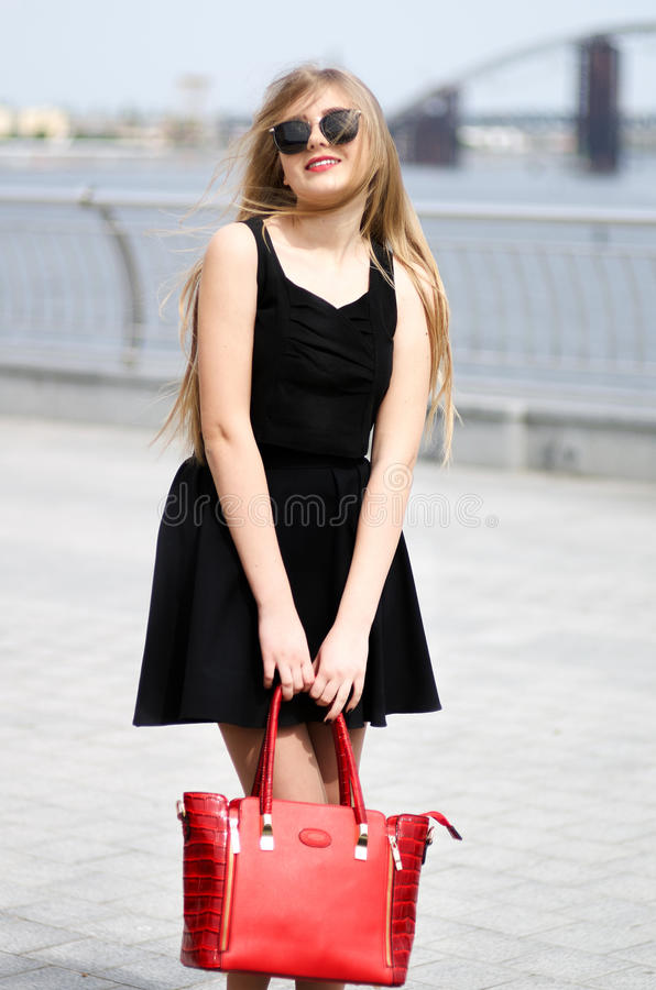 Young lady in black skirt, sleeveless shirt and fashion bag posing outdoor. Fashion portrait stock photos