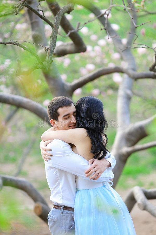 Young lady and brunette man hugging near blooming tree. stock photos