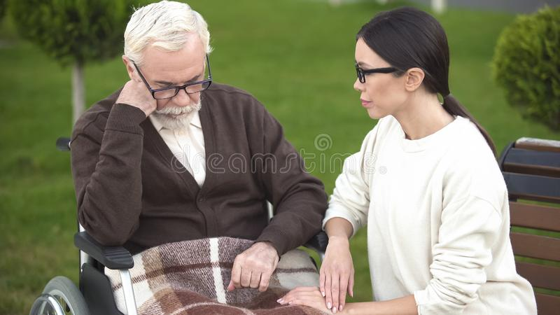Young lady comforting depressed senior male in wheelchair, psychological crisis royalty free stock image