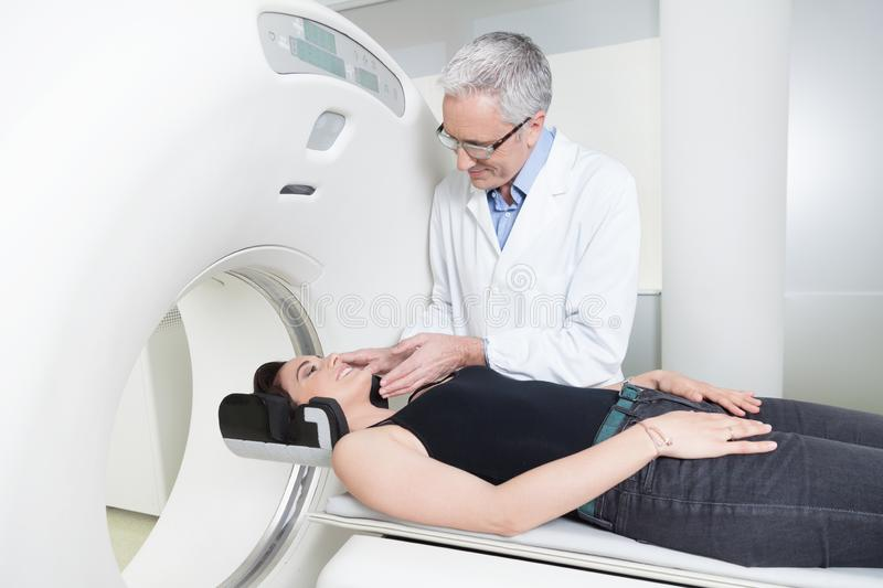 Young lady with the doctor in the room of computed tomography at hospital. Middle aged doctor in white coat explaining the benefits to a women patient the royalty free stock photos