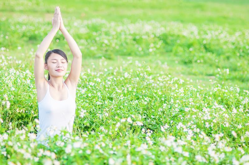 Young lady doing yoga exercise in green field outdoor area showing calm peaceful in meditation mind. Young lady doing yoga exercise in green field with small stock image