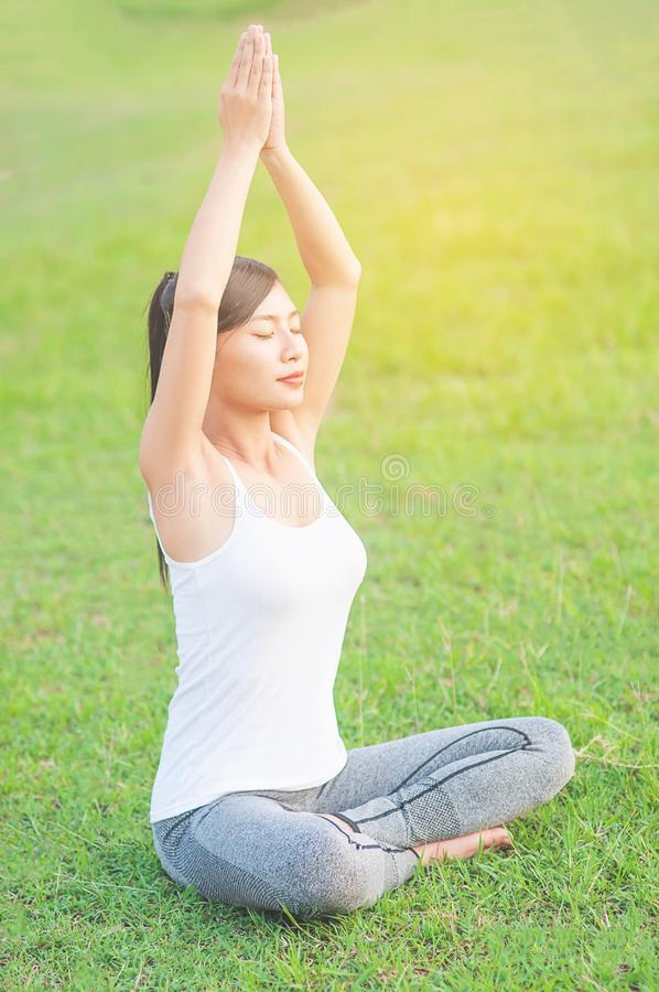Young lady doing yoga exercise in green field outdoor area showing calm peaceful in meditation mind. People practise yoga for meditation and exercise concept stock images