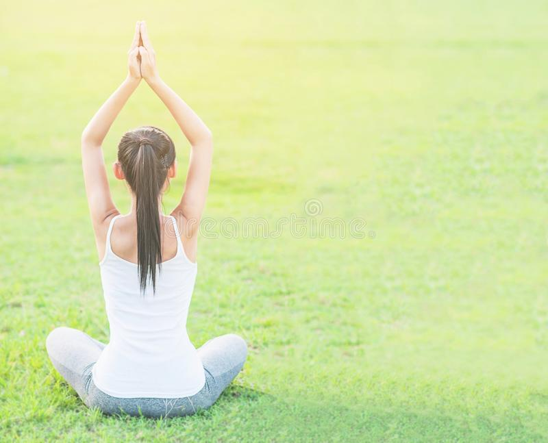 Young lady doing yoga exercise in green field outdoor area showing calm peaceful in meditation mind. People practise yoga for meditation and exercise concept stock photos