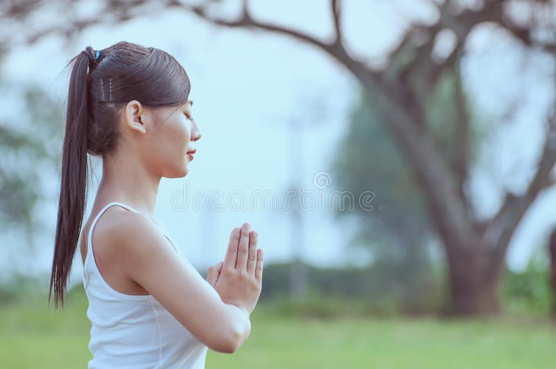 Young lady doing yoga exercise in green field outdoor. Area showing calm peaceful in meditation mind - people practise yoga for meditation and exercise concept stock photography