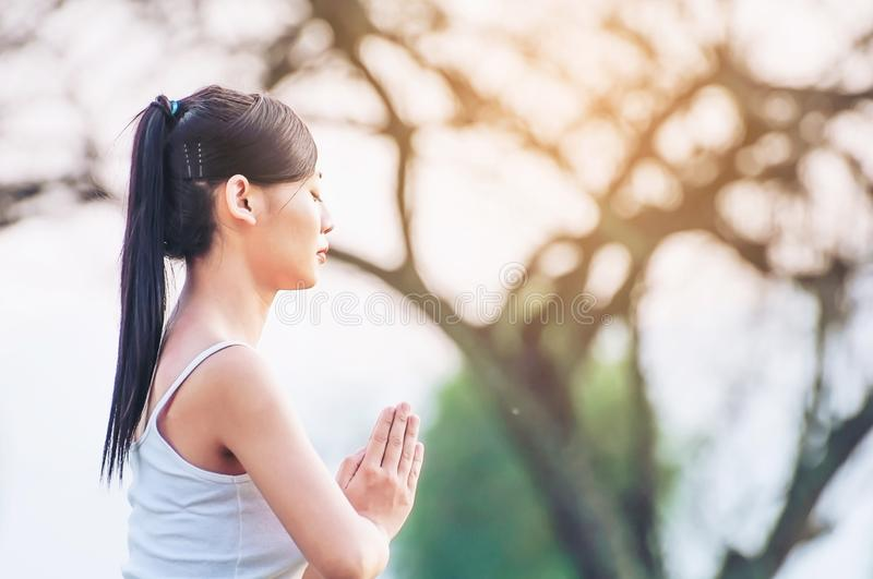 Young lady doing yoga exercise outdoor. Young lady doing yoga exercise in green field outdoor area showing calm peaceful in meditation mind - people practise royalty free stock image