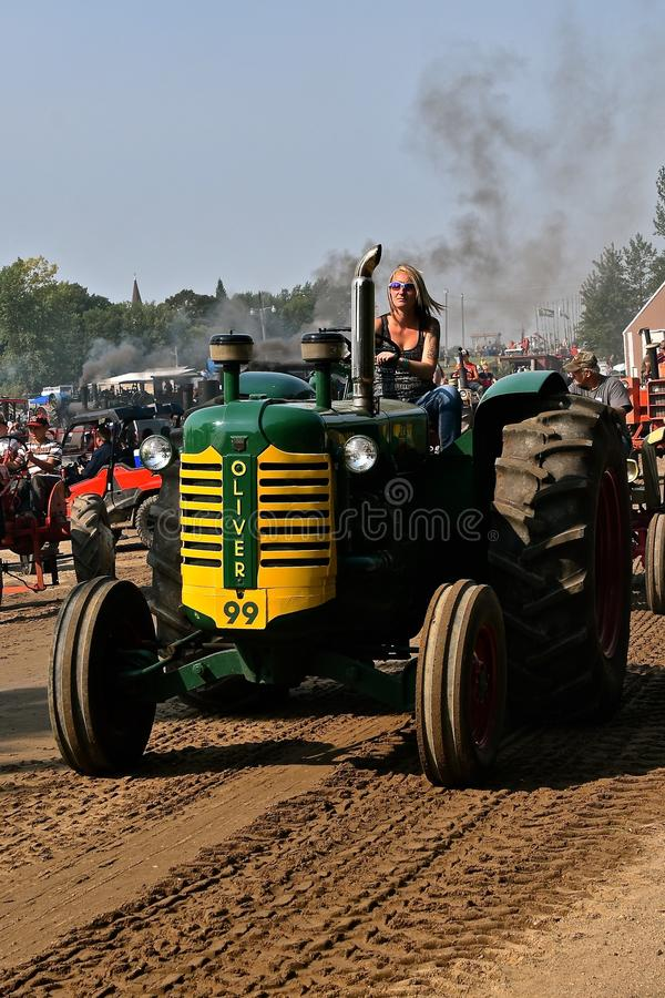 Young lady driving an Oliver 99 in a parade. ROLLAG, MINNESOTA, Sept 2, 2017: An unidentified young lady drives an old restored Oliver 99 at the annual WCSTR stock photos