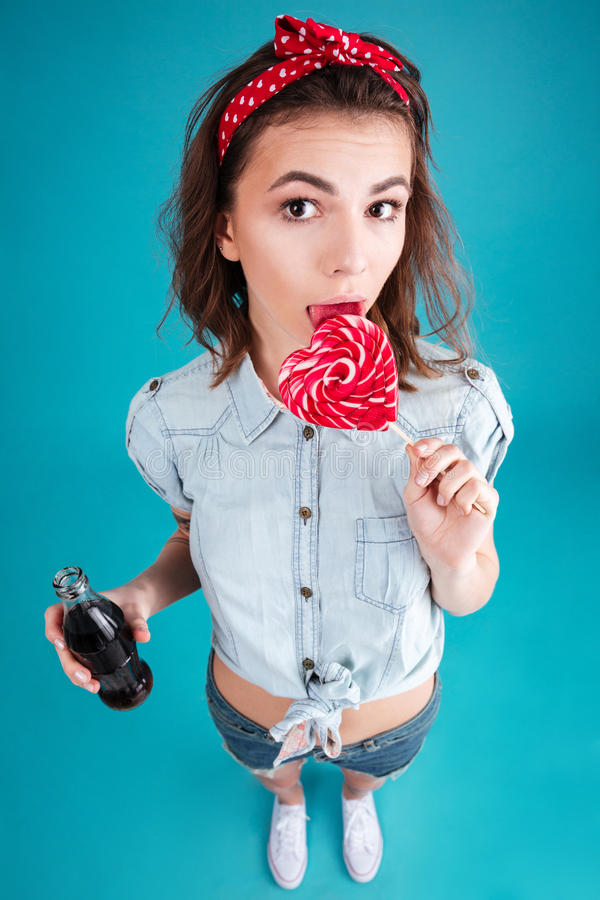 Young lady eating candy and holding aerated sweet water. Image of pretty young lady standing and posing over blue background. Looking at camera eating candy and stock image