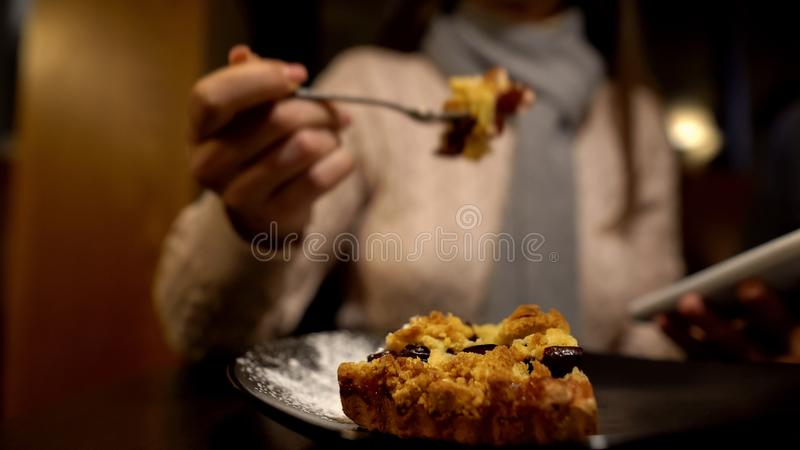 Young lady eating tasty pie and using smartphone, enjoying lunch time alone stock images