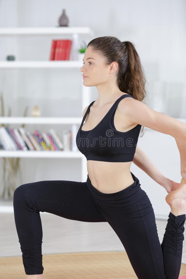 Young lady exercising at home doing leg stretch royalty free stock photos