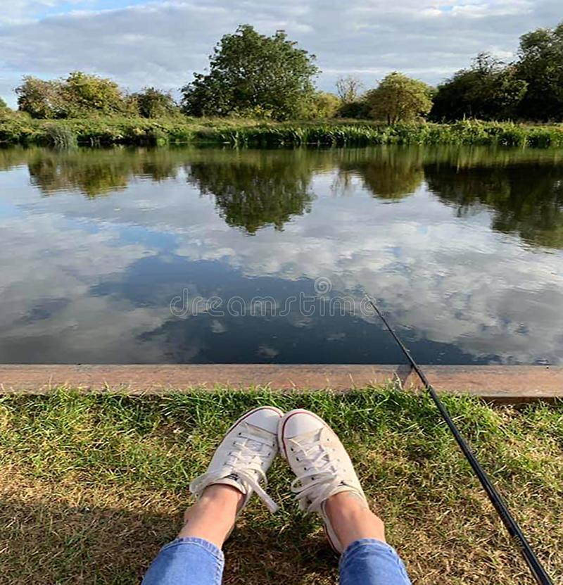 Young lady fishing and relaxing with reflextions royalty free stock images