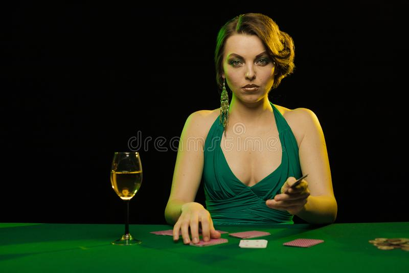 A young lady in a green dress playing cards in a casino royalty free stock images