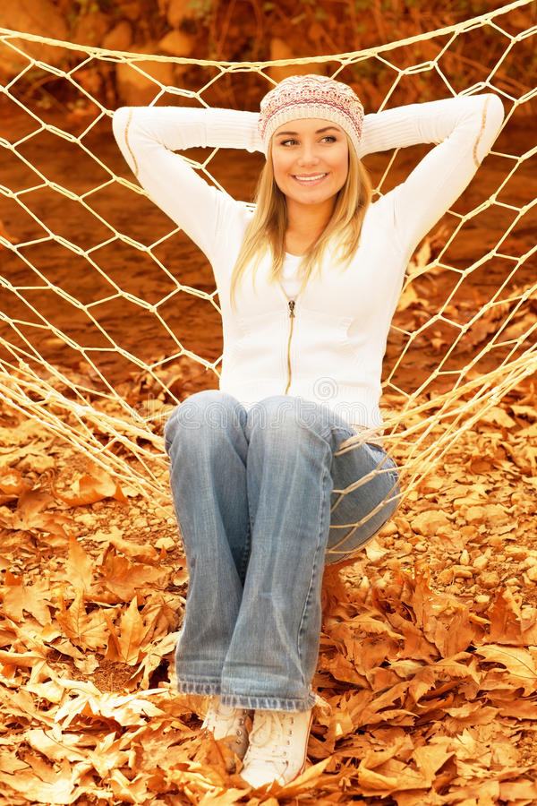 Young lady in hammock. Photo of pretty girl swinging in hammock on backyard garden, cute female wearing warm stylish hat, beautiful blond girl having fun in stock photo