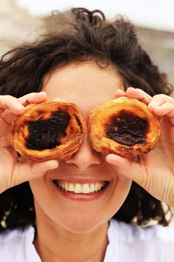 Young lady hid her eyes behind cakes. Young lady hid her eyes behind Lisbon cakes royalty free stock images
