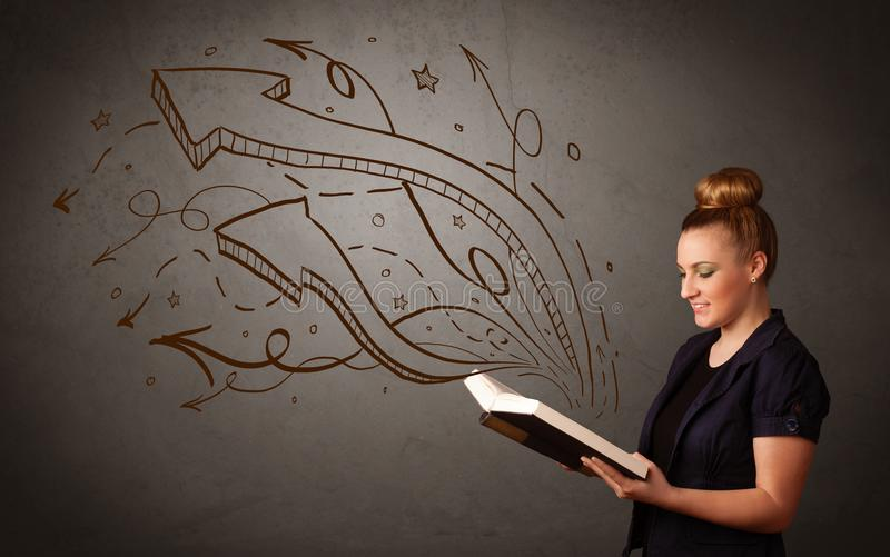 Young lady holding book with arrows. Casual young woman holding book with brown arrows and stars flying out of it stock image