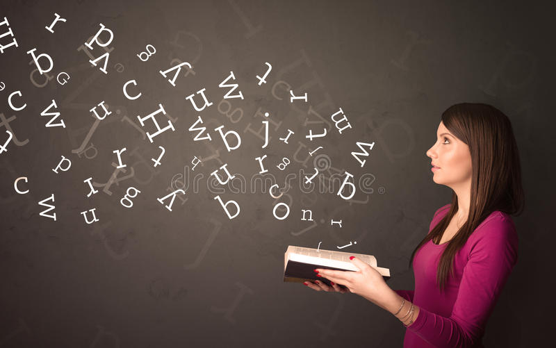 Young lady holding book with letters. Casual young woman holding book with white alphabet flying out of it royalty free stock photo