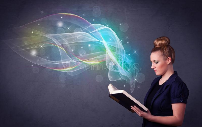 Young lady holding book with waves. Casual young woman holding book with rainbow waves flying out of it royalty free stock images