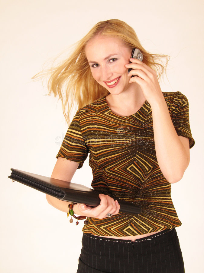 Young lady holding a cell phone. Woman holding a folder and talking on a cell phone royalty free stock images