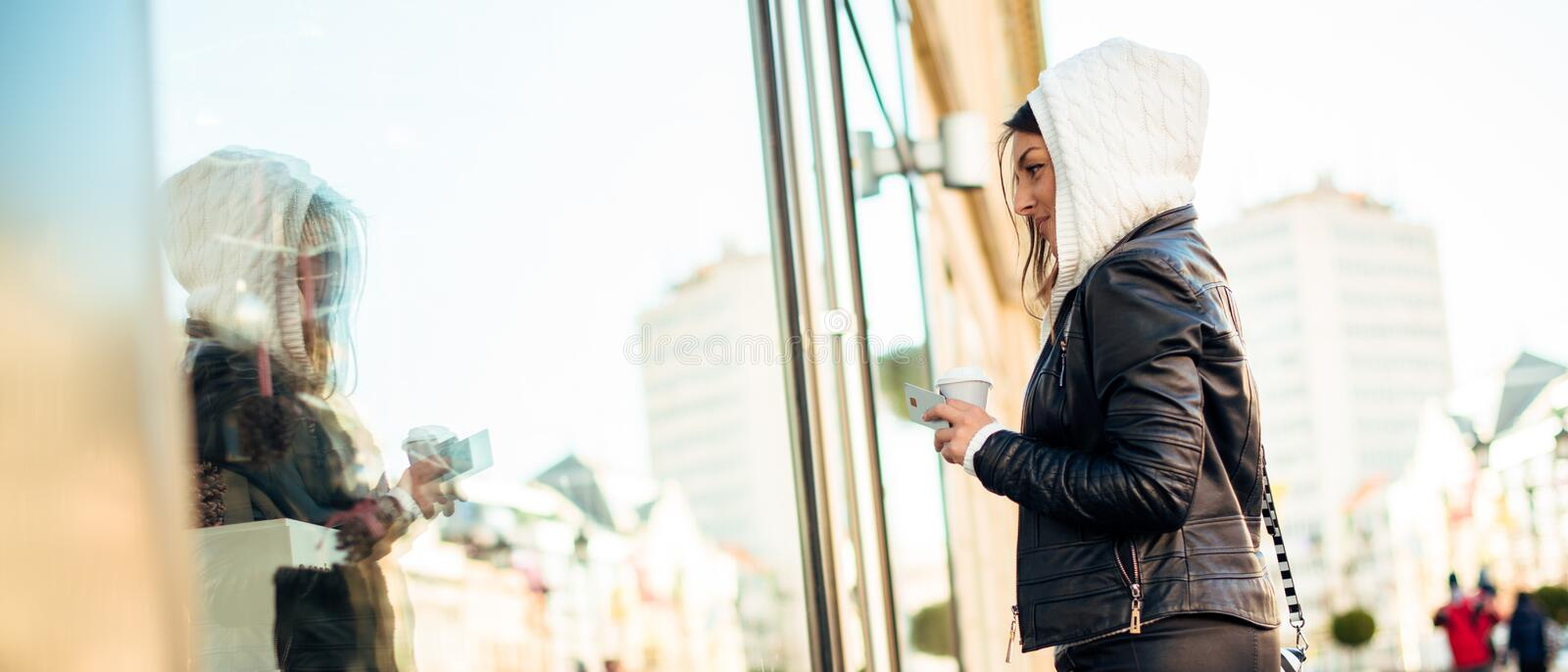 Young lady holding credit card and coffee while shopping. Looking through store window stock image