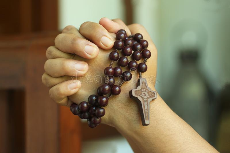 Young junior woman holding rosary in hand. Clasped hands praying holding a rosary with Jesus Christ Cross or Crucifix. royalty free stock photography